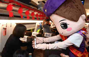 Bullet train staff perform to extend Spring Festival greetings to passengers