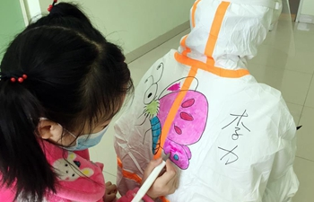 Medics draw cartoon characters on protective suits to make infected children relaxed