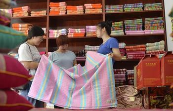 Villagers weave cloth with traditional equipment in N China's Hebei
