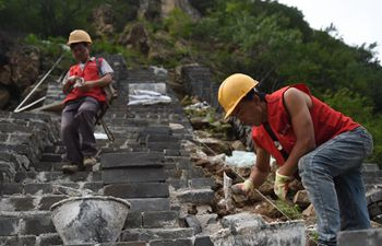 Workers repair section of Great Wall north of Donggou Village in Beijing